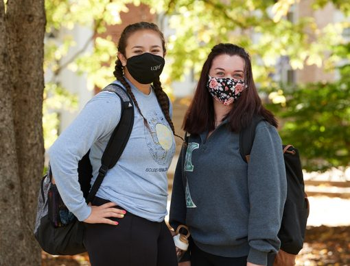 Two students standing on the Quad wearing masks.