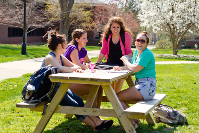 Four students working outside at a picnic table.