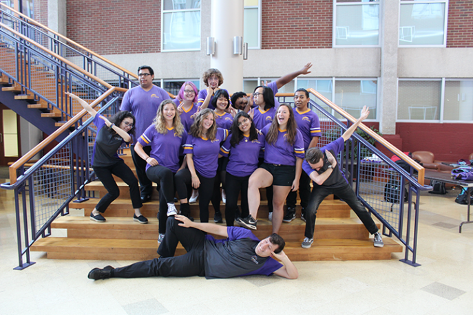 Group of students posing in matching shirts on campus.