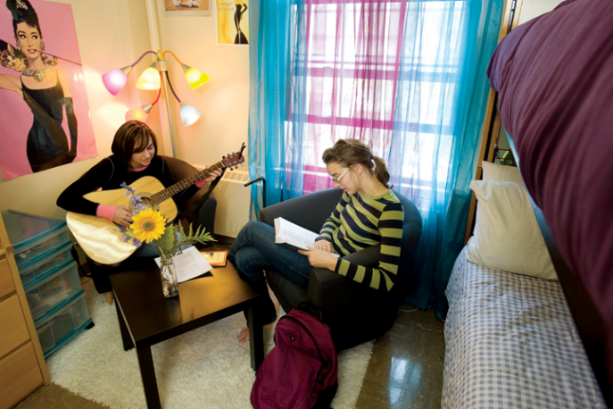 Two students spending time in a dorm room on campus.
