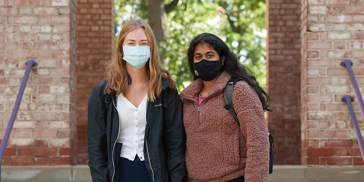 Two Albion College students wear face masks outside Baldwin Hall.