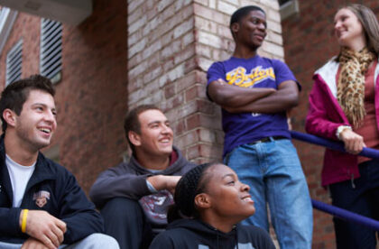 Five students outside Baldwin Hall. The three on the left are sitting on the steps, the two on the right are standing behind them.